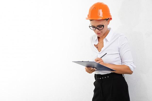Девушка в белой рубашке с оранжевым строительным шлемом подписывает документы на белом