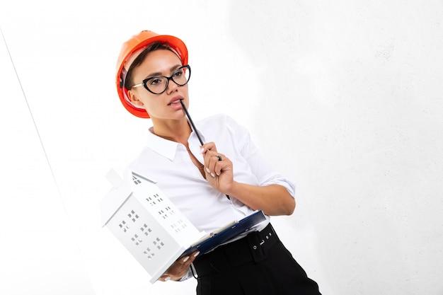 Строитель в белой классической рубашке с оранжевым строительным шлемом с документами на белом