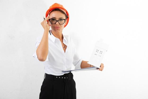 Красивый строитель девушки в белой классической рубашке с оранжевым шлемом конструкции с документами на белизне