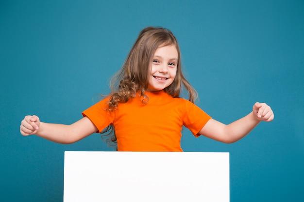 茶色の髪のティーシャツでかわいい女の子はきれいな紙を保持します。