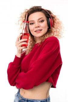 白の透明なガラスとヘッドフォンで巻き毛のブロンドの女の子の肖像画