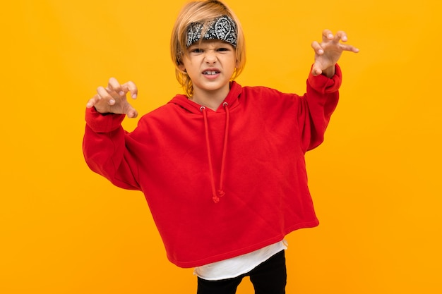 Белокурый мальчик с банданой на голове в красной куртке гримасничает на оранжевом