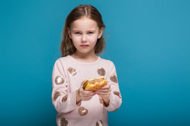 黒髪のセーターの可愛い、小さな女の子はハンバーガーを保持