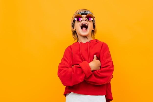 Белокурый мальчик с банданой на голове в красном свитере и очках позирует на оранжевом