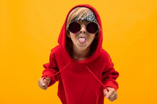 Белокурый мальчик с банданой на голове в красной балахоне в очках показывает язык на оранжевом