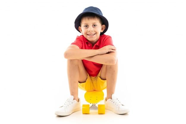 白地に黄色のスケートボードの上に座って微笑む少年