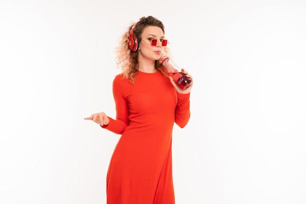 サングラスと赤いドレスでスタイリッシュな巻き毛のブロンドの女の子は音楽を楽しんで、白のカクテルを飲む