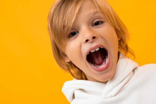 Милый белокурый мальчик кричит на желтом крупном плане студии