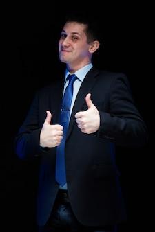 黒の背景に親指で自信を持ってハンサムな実業家の肖像画