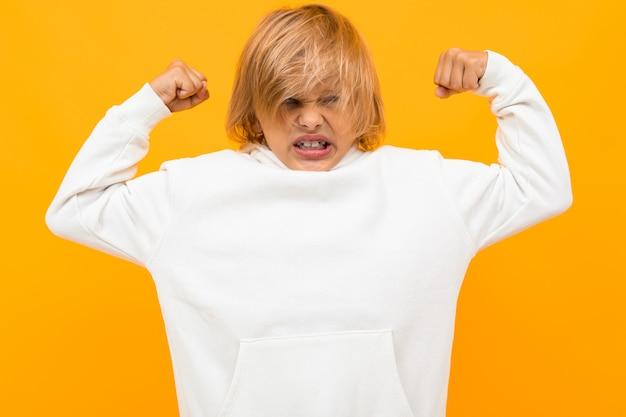 Сильный белокурый мальчик в белой толстовке на оранжевом