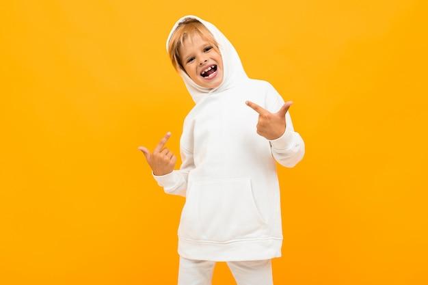 Белокурый мальчик в белом свитере морщится на желтом