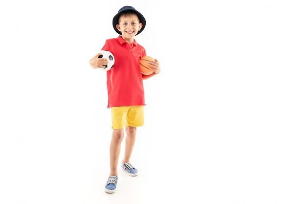 Молодой спортивный улыбающийся ребенок с футбольным мячом на белом