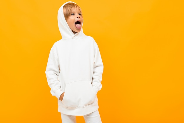 Белокурый мальчик в белом свитере морщится на оранжевом