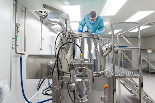 科学者は実験室の鋼鉄タンクで見る