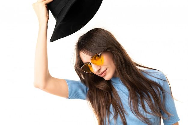 楽しい笑顔と白い壁に分離された黒い帽子笑顔を持つ少女