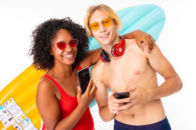 Улыбающаяся пара европейский парень и африканская девушка в купальниках с очками и наушниками и телефонами в руках