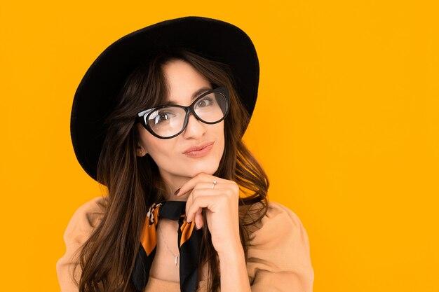 Какавская модель брюнетки в очках, шляпе и шейном платке позирует на желтой стене
