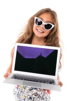 サングラスとラップトップ、白い壁に分離された画像を持つかなり白人少女