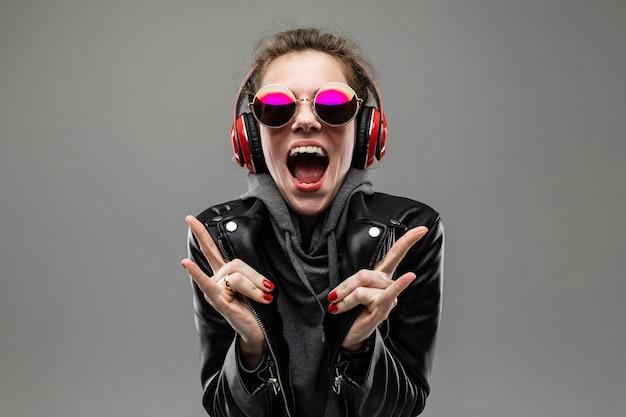 Улыбающаяся дерзкая девушка слушает музыку в красных наушниках на серой стене