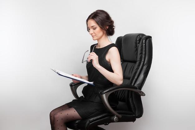 Картина красивая женщина в черном платье с планшетом в руках