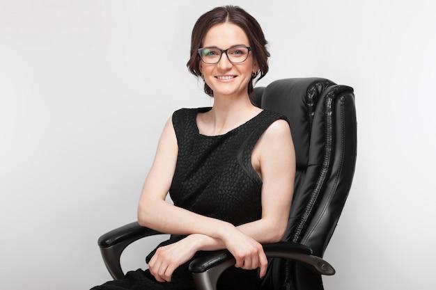 Картина красивая женщина в черном платье, сидя на кресле