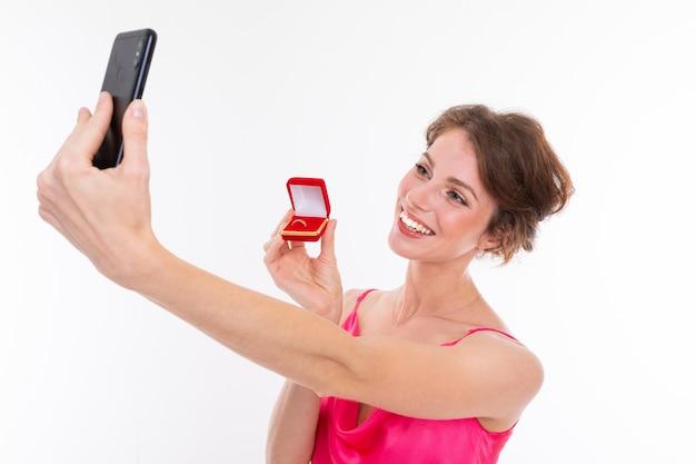 Красивая кавказская женщина делает селфи с брачным кольцом, фотография, изолированная на белой стене