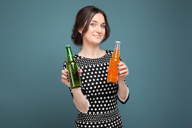 Картина привлекательная женщина в крапчатой одежде, стоя с содой и пивом в руках