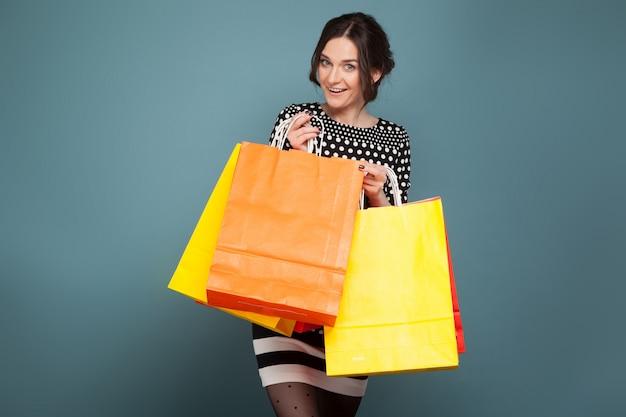 Образ красивой женщины в крапчатую одежду, стоя с покупками в руках