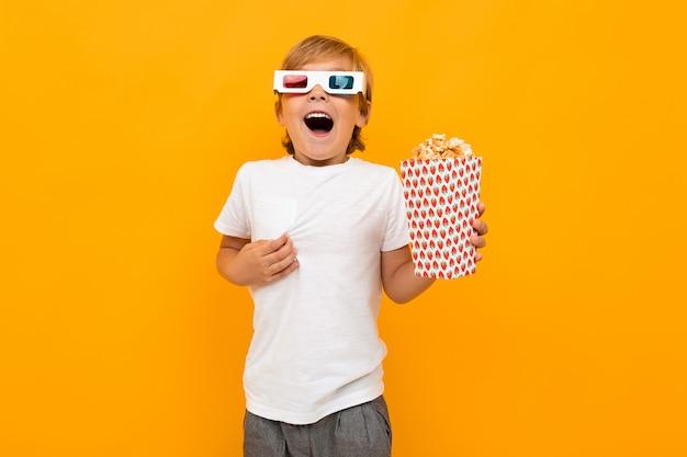 Мальчик в очках для кинотеатра с попкорном с удивлением смотрит фильм на желтой стене