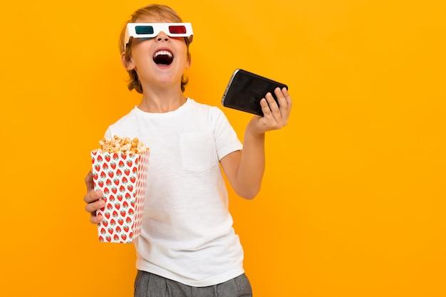 Удивленный мальчик в очках для кинотеатра с попкорном и телефоном на желтой стене