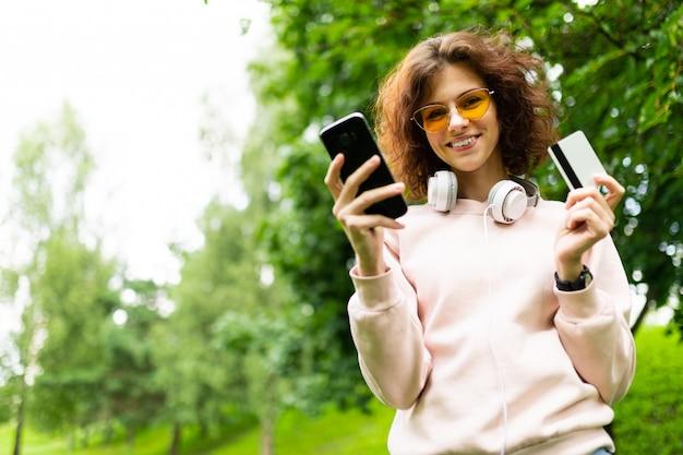 電話と緑豊かな公園の壁にクレジットカードを持つ魅力的な女の子
