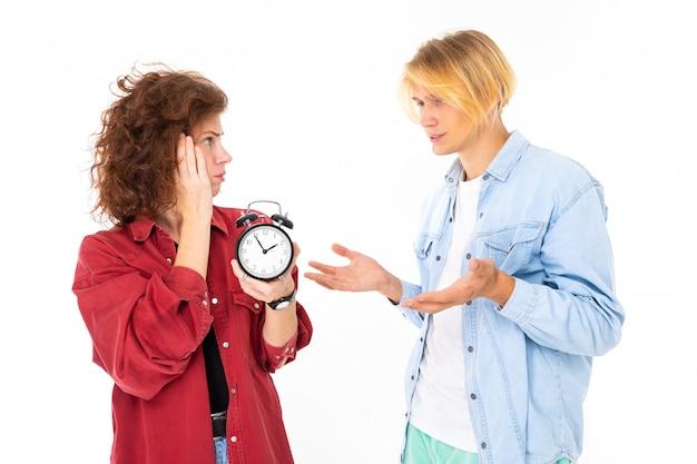 目覚まし時計と恋にカップルが白い壁に分離された時間について主張します。
