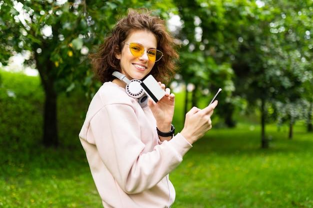 電話と緑豊かな公園の壁にクレジットカードを持つ魅力的なヨーロッパの女の子