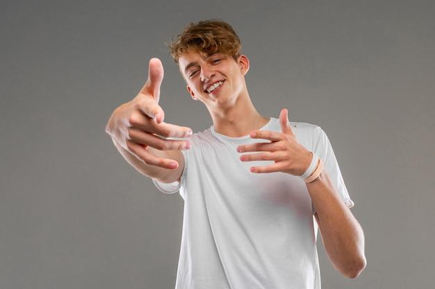 Кавказский милый парень в белой футболке показывает руки на серую стену
