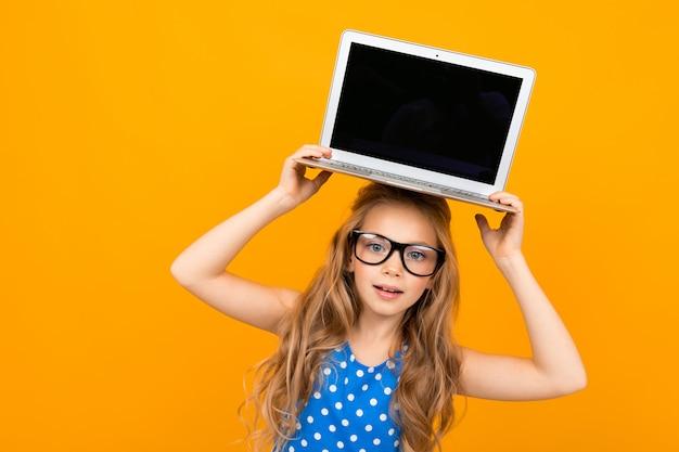 彼女のメガネで素敵な女の子はラップトップと白い壁に分離された笑顔を保持しています。