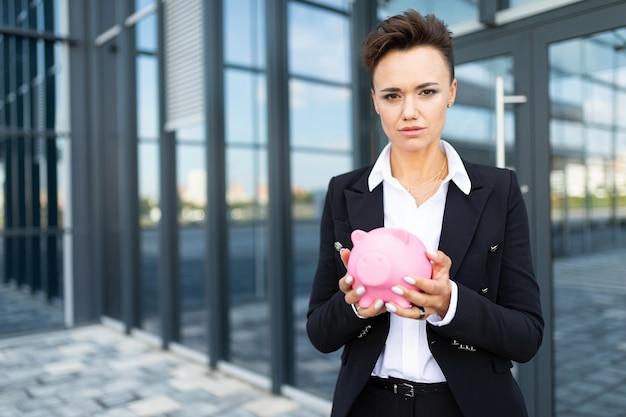 Кавказская женщина в офисной одежде держит розовую свинью-копилку и ждет коулигу возле офисного здания