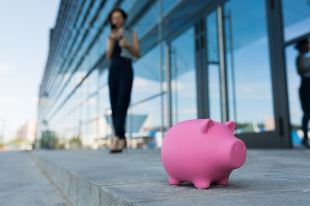 Бизнес женщина, держащая ноутбук на открытом воздухе с розовой свиньей копилки
