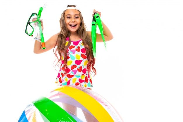 Девушка держит очки и подводное плавание с аквалангом возле надувной мяч на белой стене