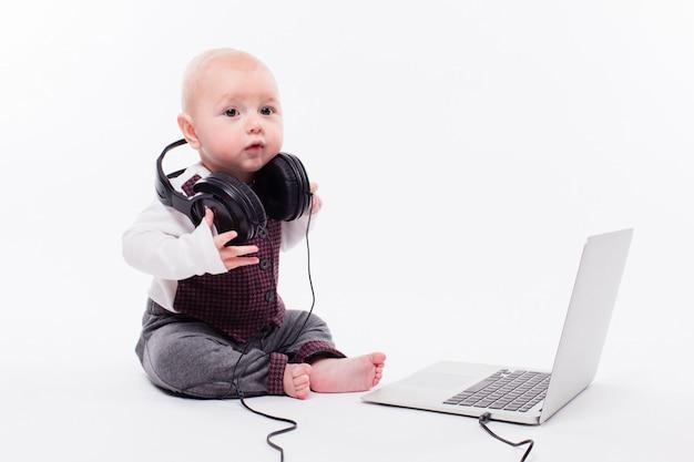 Милый ребенок сидит перед ноутбуком в наушниках