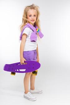 Белокурая маленькая девочка со спортивной курткой на плечах держит скейтборд на белой стене