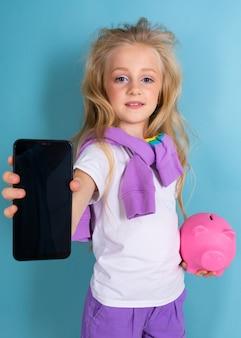 水色の壁にピンクの貯金箱モックアップと電話で魅力的なブロンド少女
