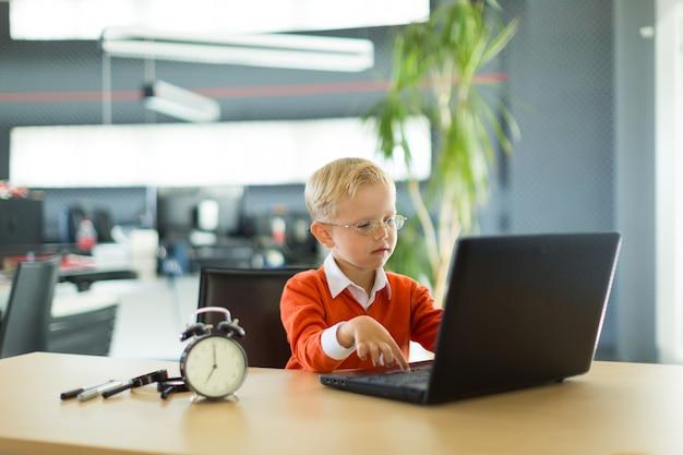 かわいい男の子はオフィスの机に座って、コンピューターを使用