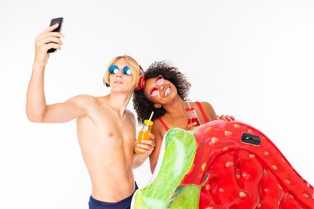 Довольно африканская женщина и кавказский белокурый мужчина стоят в купальниках с резиновыми пляжными матрасами, пьют сок и делают селфи вместе на белом фоне