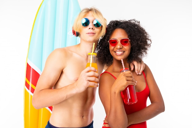 Довольно африканские женщины и кавказские блондин человек стоит в купальнике с резиновыми пляжными матрасами, пьет сок и улыбки, изолированных на белом фоне