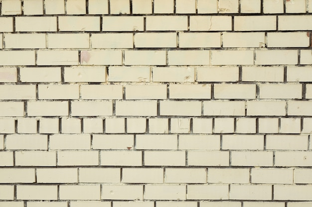 隙間に暗い灰色のコンクリートで汚れた白いレンガの壁