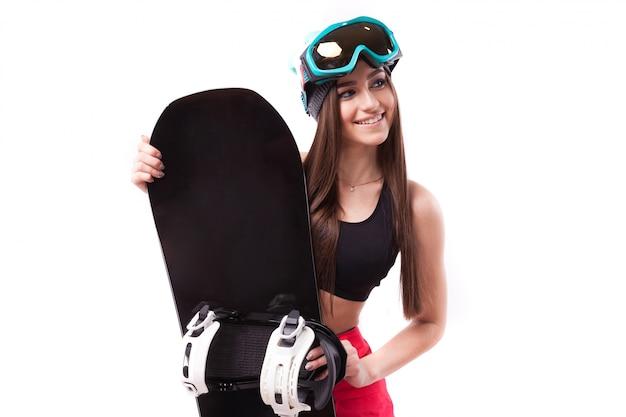 黒の短いタンクトップで若いきれいな女性がスノーボードを保持します。
