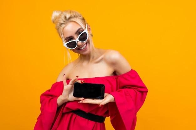 赤いドレスの魅力的な女の子は黄色の壁に空白の画面の電話テンプレートを示しています