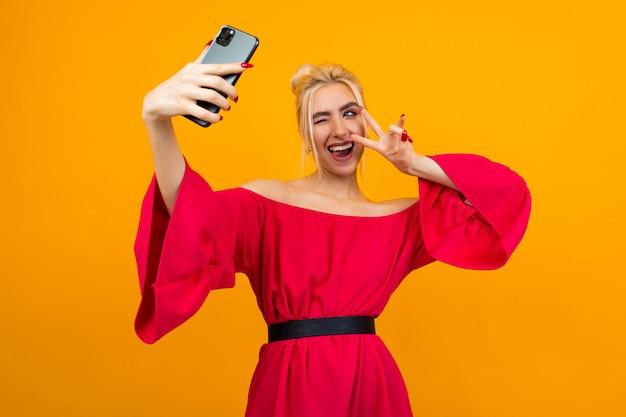 Молодая улыбающаяся женщина в элегантном красном платье делает селфи на смартфоне на желтой стене