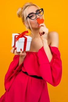 赤いドレスの魅力的なヨーロッパの女の子はオレンジ色の壁にギフトボックスと赤い紙のハートを保持します