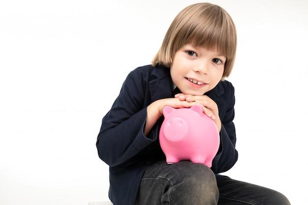 Довольно подросток мальчик в черном костюме сидит с копилкой розовый свинья, изолированных на белом фоне
